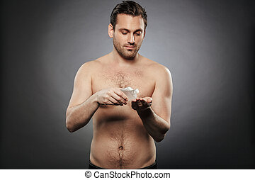 Portrait of a smiling shirtless man using aftershave lotion