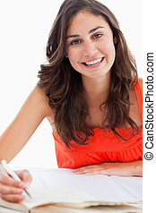 Portrait of a smiling student doing her homework