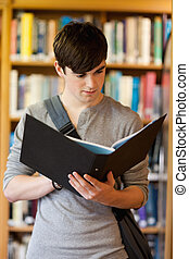 Portrait of a smiling student looking at a binder