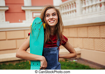 Portrait of a smiling teenage girl holding a skateboard