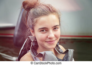 portrait of a smiling teenage girl with lifejacket