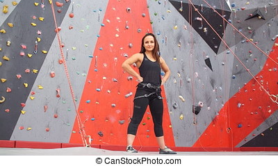 Portrait of a smiling woman climber climbs indoors in...