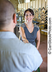 portrait of a smiling woman giving an handshake to customer