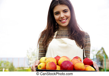 Portrait of a smiling woman holding basket with apples in garden
