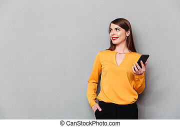 Portrait of a smiling woman holding mobile phone