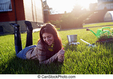 Portrait of a smiling woman lying on green grass