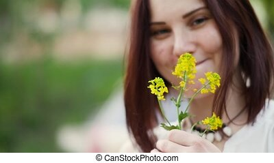 Portrait of a smiling woman outdoors. Yellow flowers in the hands of women