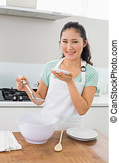 Portrait of a smiling woman preparing food in kitchen