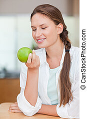 Portrait of a smiling woman with an apple