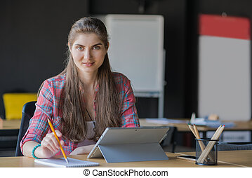 Portrait of a Smiling Woman Writing in the Notebook while Working on Laptop lndoors.