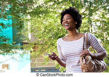 smiling young african woman walking with mobile phone and purse