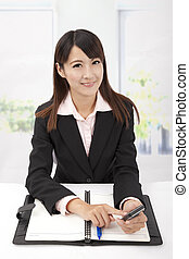 Portrait of a smiling young business woman holding touch phone in the office