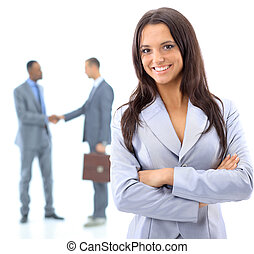 Portrait of a smiling young business woman with people discussing in background