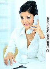 Portrait of a smiling young business woman speaking on mobile phone while using laptop in office