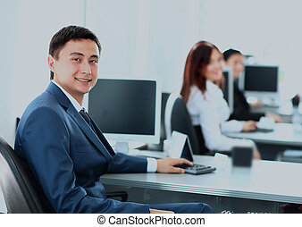 Portrait of a smiling young businessman working on computer at office with his colleagues.