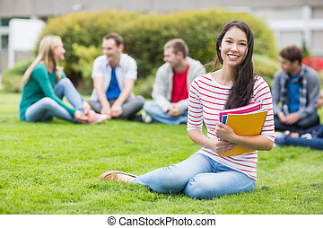 Portrait of a smiling young college student with blurred friends sitting in the park