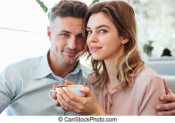 Portrait of a smiling young couple drinking coffee