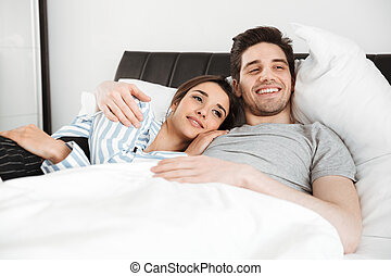 Portrait of a smiling young couple lying