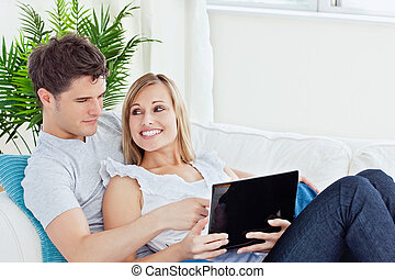 Portrait of a smiling young couple sitting on a sofa using...