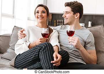 Portrait of a smiling young couple relaxing on a couch