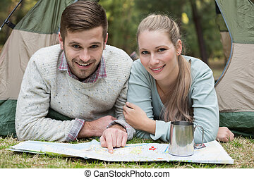 Portrait of a smiling young couple with map in tent