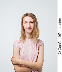 Portrait of a smiling young european woman standing with arms folded