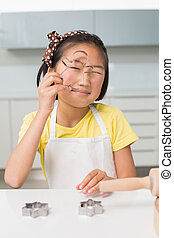 Portrait of a smiling young girl holding cookie mold in kitchen