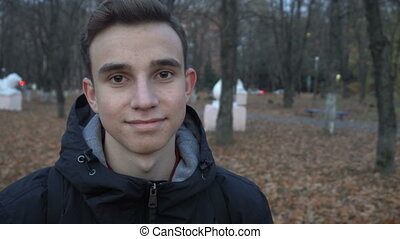 portrait of a smiling young man standing in autumn Park