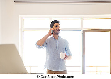 Portrait of a smiling young man talking on mobile phone