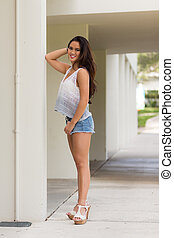 Portrait of a smiling young pretty Asian girl with long brown hair in jean shorts and high heel sandals