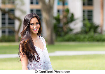 Portrait of a smiling young pretty Asian girl with long brown hair