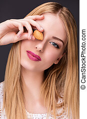 Portrait of a smiling young woman holding an almond in front of her eye