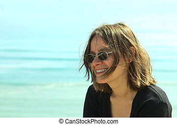 Portrait of a smiling young woman in sunglasses on the coast (Selective Focus, Focus on the left side of the face)