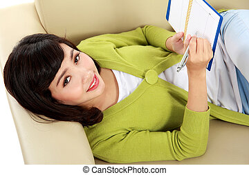 smiling young woman lying on sofa and writing