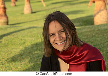 Portrait of a smiling young woman with a red scarf in a park in the evening light (Selective Focus, Focus on the face of the woman)