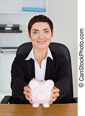 Portrait of a smilling office worker holding a piggybank