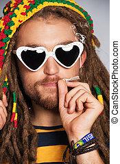 Portrait of a smoking rastafarian young man.