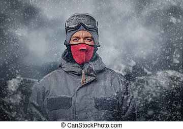 Portrait of a snowboarder dressed in a full protective gear for extream snowboarding posing at a studio.