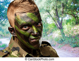 portrait of a soldier with camouflage painting