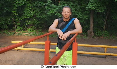Portrait of a sportsman having a break after workout outdoors, young sporty guy resting after training sitting on sports ground