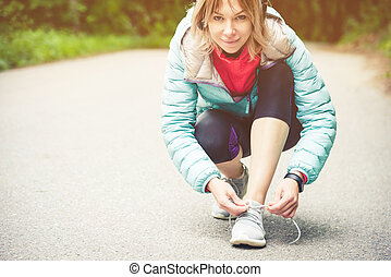 Portrait of a sporty blonde girl in headphones on a run in the forest. A girl sitting tied shoelaces on cross-country shoes. Active lifestyle. Sport