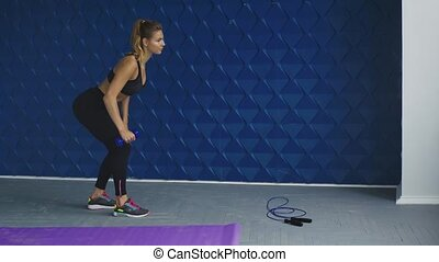 Portrait of a sporty woman doing lunges with dumbbells, working out legs muscles