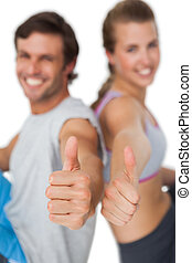 Portrait of a sporty young couple gesturing thumbs up