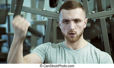 Portrait of a strong man who pulls weight with one hand on a training machine.