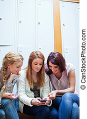 Portrait of a student showing a text message to her friends
