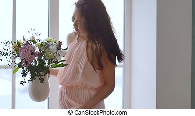 Portrait of a stunningly beautiful Asian young woman in a delicate pink dress with spring flowers in her hands. A woman dances and enjoys flowers in a bright room in the morning sun. Slow motion