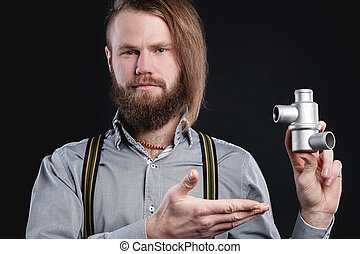 Portrait of a stylish bearded long-haired male salesman and dealer spare parts of the car in a shirt and suspenders. Holding a stainless steel engine cooling thermostat