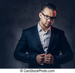 Portrait of a stylish businessman with serious face in an elegant formal suit and glasses.