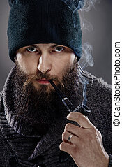 Portrait of a man with a beard the smoking a pipe. A man looks like a sailor - Captain, wearing a thick sweater and a black cap.