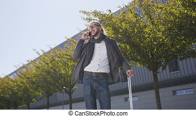 Portrait of a stylish young business man in jacket with suitcase who walking near business building, communicates via smartphone. Outdoors. Concept of new business, banker, communication, manager, business trip